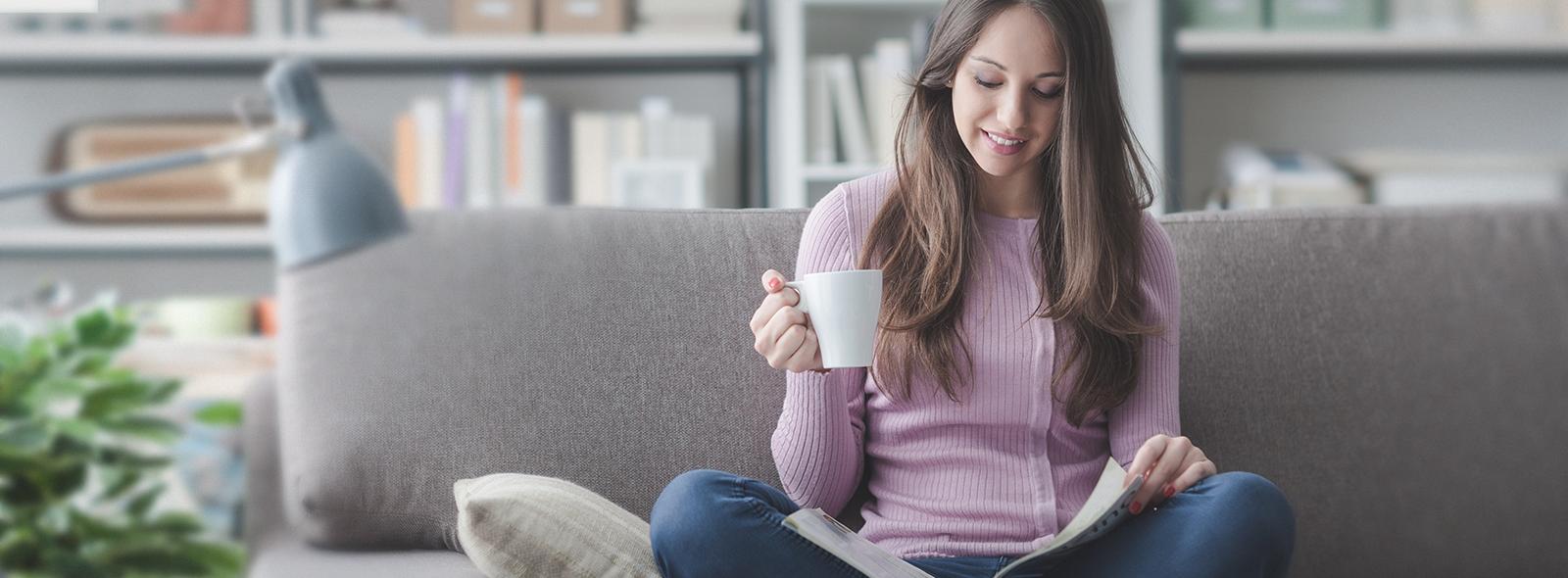 Junge Frau liest Zeitschrift mit Kaffee auf dem Sofa